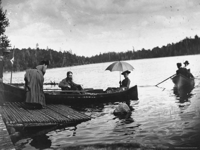 two-couples-sitting-in-rowboats-on-a-lake-as-a-man-and-woman-watch-from-a-small-dock